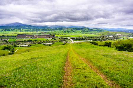 Hiking trail descending into the valley; Aerial view of agricultural fields and mountains in the  background, south San Francisco bay, San Jose, California