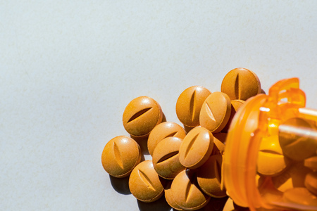 Yellow prescription pills spilled onto a table. Concept of opioid addiction and healthcare industry