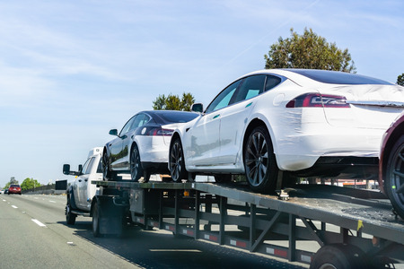 April 26, 2019 Redwood City  CA  USA - Car transporter carries Tesla Model 3 new vehicles along a highway in San Francisco bay area, back view of the trailer;