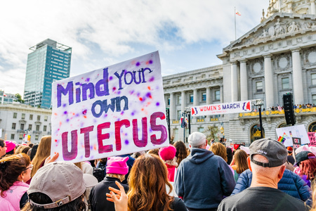 """January 19, 2019 San Francisco / CA / USA - Participant to the Women's March event holds """"Mind your own uterus"""" sign at the rally held in front of the City hall building"""