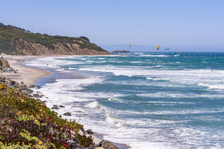 The Pacific Ocean coastline close to Santa Cruz, California; unidentified people windsurfing on a sunny day at Waddell Beach