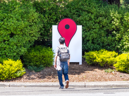 June 4, 2019 Mountain View  CA  USA - The Google Maps Icon near their offices in the Google campus in Silicon Valley; employee crossing the street
