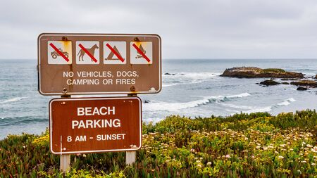 """""""No vehicles, dogs, camping or fires"""" sign and beach parking hours posted at a beach on the Pacific Ocean coastline on a cloudy day, California"""