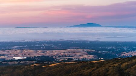 Clouds and fog at twilight over Silicon Valley and the San Francisco bay area; Stanford University visible under a layer of clouds; Mt Diablo in the background; Imagens