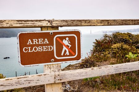 Area Closed sign posted on the Pacific Ocean coast in Marin Headlands, Marin County; Golden Gate Bridge engulfed by fog visible in the background; San Francisco, California