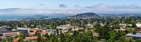 View towards Berkeley, Richmond and the San Francisco bay area shoreline on a sunny day; University of California Berkeley campus buildings in the foreground, California