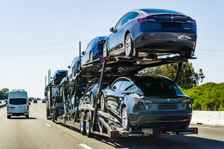 July 4, 2019 Redwood City / CA / USA - Car transporter carries Tesla Model 3 new vehicles along the highway in San Francisco bay area, back view of the trailer; Redakční