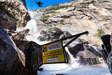 Warning sign due to Wapama Falls flowing over the footbridge and creating hazardous conditions for crossing; Hetch Hetchy Reservoir area, Yosemite National Park, California