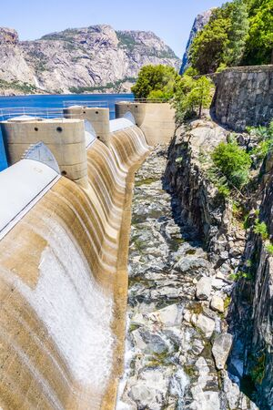 Water flowing through the OShaughnessy Dam spillway due to high water levels in the Hetch Hetchy reservoir, Yosemite National Park, Sierra mountains, California
