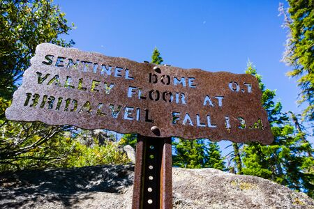 Hiking trail sign posted on the trail to Sentinel Dome, close to Glacier Point, showing points of interest and distances; Yosemite National Park, Sierra Nevada mountains, California