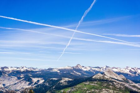 Multiple contrails cross paths through the blue sky above snow capped mountains; Yosemite National Park, Sierra Nevada mountains, California