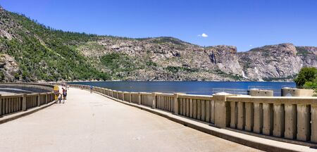 Paved road on top of O'Shaughnessy Dam; Hetch Hetchy Reservoir visible on the right; Yosemite National Park; Hetch Hetchy Valley is a source of drinking water for San Francisco Bay area, California