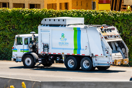 July 19, 2019 Mountain View / CA / USA - Recology vehicle driving on the freeway, heading to a landfill; Recology is providing garbage hauling and recycling services to local residents and business