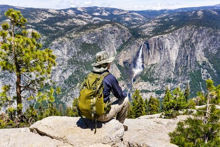 Unidentified hiker sitting on a rock and looking towards Yosemite Valley and Upper Yosemite Falls, Yosemite National Park, California Banco de Imagens