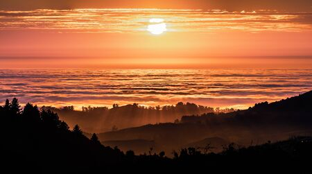 Brightly colored sunset in the Santa Cruz mountains, layered hills and valleys visible in the foreground and sea of clouds in the background; San Francisco Bay Area, California