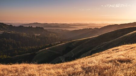 Sunset view of layered hills and valleys; sea of clouds visible in the background; Santa Cruz mountains, San Francisco bay area, California Banco de Imagens