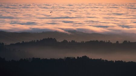 Sunset view of layered hills and valleys covered by a sea of clouds in Santa Cruz mountains; paraglider visible above the clouds; San Francisco bay area, California