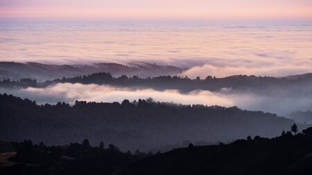 Sunset view of layered hills and valleys covered by a sea of clouds in Santa Cruz mountains ; San Francisco bay area, California Banco de Imagens