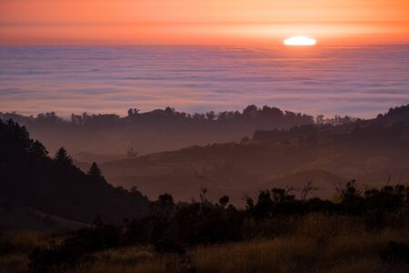 Sun setting over a sea of clouds; layered hills and valleys visible in the foreground; Santa Cruz mountains, San Francisco Bay Area, California
