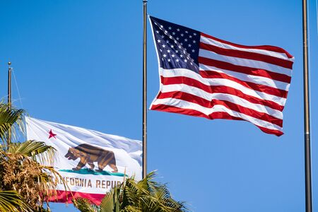 August 1, 2019 Santa Clara / CA / USA - Beautifully waving star and striped American flag and the Republic of California flag on a blue sky background;