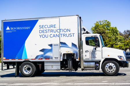 July 12, 2019 Santa Clara  CA  USA - Iron Mountain vehicle driving on a street; Iron Mountain Inc. is an American company that provides records management and data destruction, backup and recovery