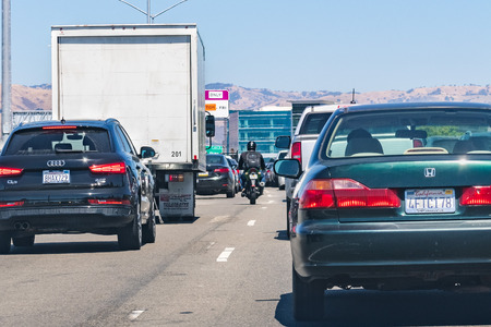 August 1, 2019 San Jose  CA  USA - Heavy traffic on one of the freeways crossing Silicon Valley; motorcyclist splitting lanes visible among cars Редакционное