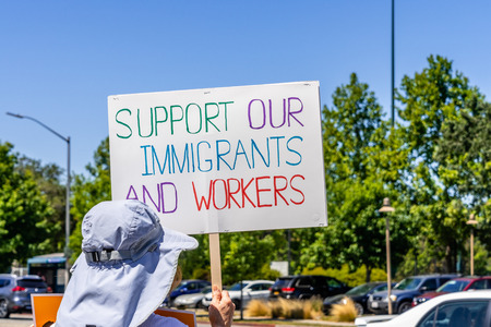 July 26, 2019 Palo Alto  CA  USA - Protester holding a sign with the message Support our immigrants and workers