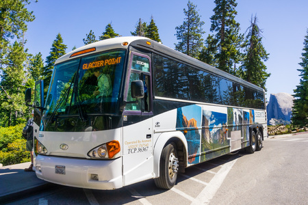 June 27, 2019 Yosemite National Park / CA / USA - The Yosemite Glacier Point guided tour bus, operated by Aramark, available from late May to early November; Half Dome visible in the background Banco de Imagens - 128407192