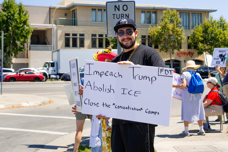 July 26, 2019 Palo Alto  CA  USA - Protester holding a sign with the messages Impeach Trump, Abolish ICE and Close the concentration camps