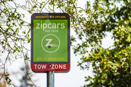 August 8, 2019 Palo Alto / CA / USA - Zipcars reserved parking sign in a parking lot in Silicon Valley; Zipcar is a car sharing and car club service where members pay a monthly fee Banco de Imagens - 128407233