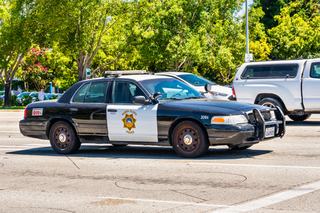 August 9, 2019 Santa Clara / CA / USA - Santa Clara police department vehicle driving on the streets in South San Francisco Bay Area in an old fashioned Ford vehicle Standard-Bild - 128407237