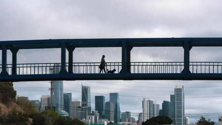 Woman walking her dog on a pedestrian overpass on a cloudy day; San Francisco financial district skyline visible in the background
