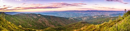 Panoramic view towards San Jose and south San Francisco bay at sunset; Hills and valleys in the Santa Cruz mountains in the foreground; Diablo Range visible on the other side of the valley, California Stock Photo