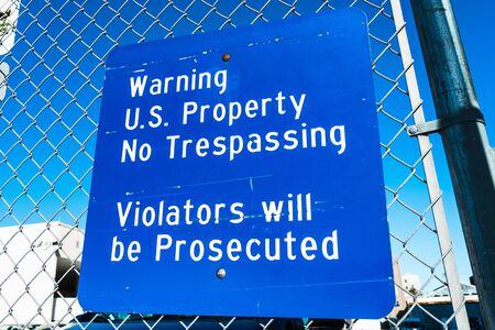 Posted Warning US Property No Trespassing; Violators will be Prosecuted sign at a federal facility in San Francisco, California