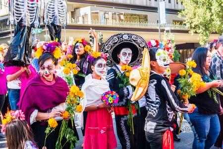 Oct 20, 2019 San Jose / CA / USA - Participants at Dia de Los Muertos (Day of the Dead) procession wearing sugar-skull make-up; South San Francisco Bay