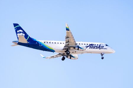 Oct 20, 2019 San Jose  CA  USA - Alaska Airlines aircraft flying approaching Norman Y. Mineta San Jose International Airport and preparing for landing; blue sky background