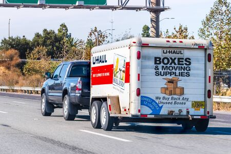 Oct 26, 2019 Mountain View  CA  USA - Semi truck towing an U-Haul cargo trailer, on a freeway in San Francisco bay area; U-Haul is an American moving equipment and storage rental company