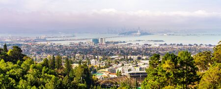 Panoramic view of Berkeley; San Francisco Bay shoreline with Port of Oakland, Yerba Buena Island, Treasure Island, the Bay bridge and the San Francisco skyline visible in the background; California