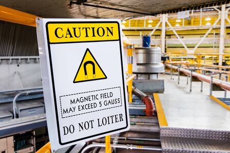 Magnetic field hazard symbol posted in a laboratory; Warning posted: 'Caution; Magnetic field may exceed 5 Gauss; Do not loiter