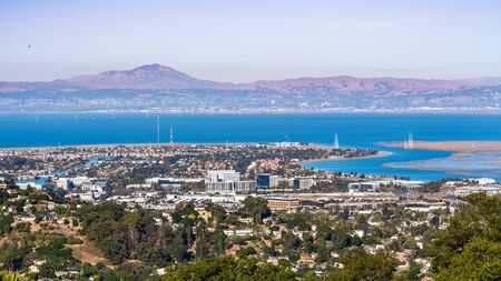 Aerial view of San Carlos and Redwood Shores; East Bay and Mount Diablo in the background; houses visible on the hills and close to the shoreline; office buildings built close to downtown San Carlos Banco de Imagens