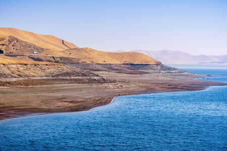 The shoreline of San Luis Reservoir, an artificial lake storing water for agricultural purposes in Central California; visible low water level towards the end of fall; Merced County, California;