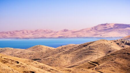 High angle view of San Luis Reservoir, an artificial lake storing water for agricultural purposes in Central California; Hills covered in dry grass in the foreground; Merced County, California; Stock Photo