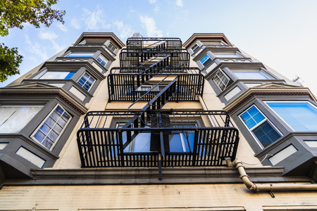Exterior view of multifamily residential building; Old metal fire escape stairs hanging on side of the building; Berkeley, San Francisco Bay Area, California Editorial