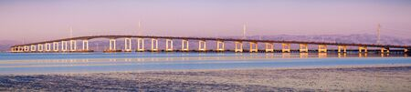 Panoramic view of San Mateo Bridge at sunset; electricity towers and power lines visible behind it; the San Mateo Bridge is connecting the Peninsula and East Bay in San Francisco Bay Area, California Stock fotó - 134900051