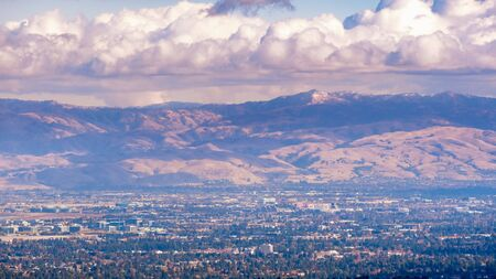 Aerial view of Santa Clara and South San Jose, Silicon Valley, San Francisco Bay Area, California; Diablo mountain range with a dusting of snow covering the peaks visible in the background; cloudy sky