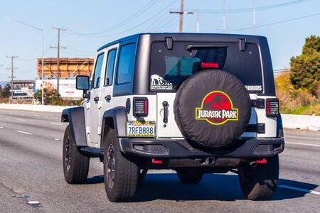 Dec 28, 2019 Redwood City  CA  USA - Jeep vehicle driving on a freeway in San Francisco Bay Area; Jurassic Park themed cover used for the spare wheel; Editorial