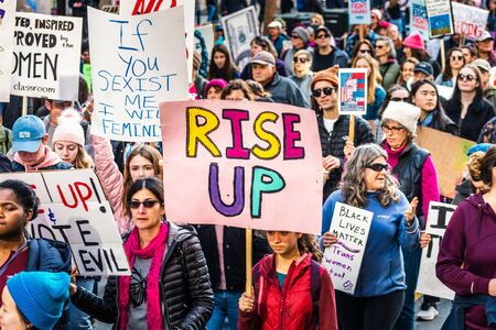 Jan 18, 2020 San Francisco  CA  USA - Participant to the Womens March event holds Rise Up sign while marching on Market street in downtown San Francisco