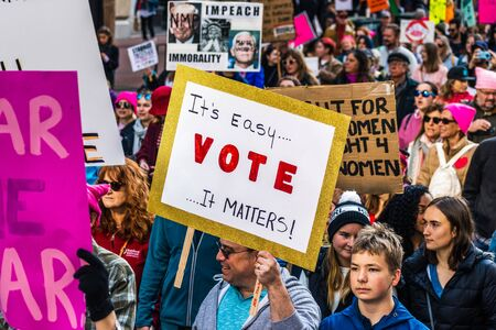 Jan 18, 2020 San Francisco  CA  USA - Participant to the Womens March event holds Its easy...VOTE...it matters! sign while marching on Market street in downtown San Francisco