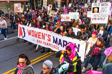 Jan 18, 2020 San Francisco  CA  USA - Participants to the Womens March event hold signs with various messages while marching on Market street in downtown San Francisco