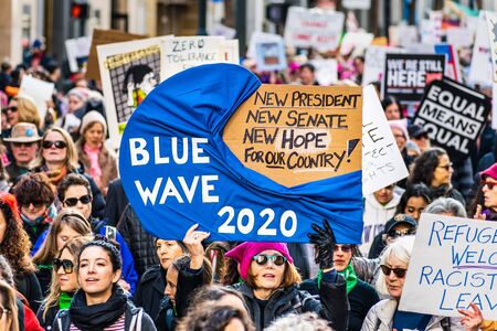 Jan 18, 2020 San Francisco  CA  USA - Participant to the Womens March event holds Blue Wave 2020 sign while marching on Market street in downtown San Francisco